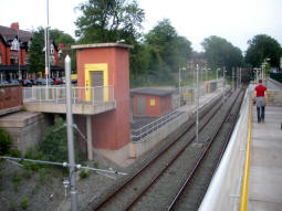 A view of the platform for trams to East Didsbury and the lift to it from the ramp towards the other platform